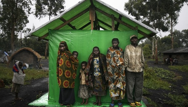 A group of pygmies shelter from the rain in Mubambiro village near Goma