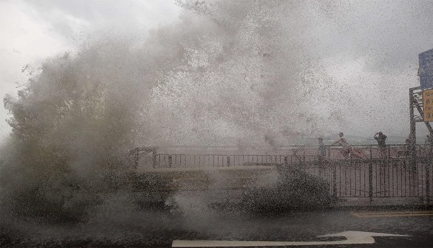 People (back R) are sprayed by water from a crashing wave