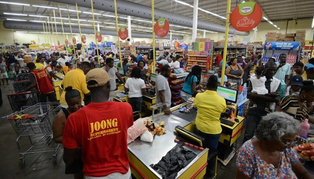 People buy groceries and supplies before the arrival of Hurricane Matthew in Portmore, Jamaica