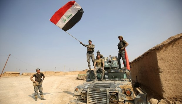 Iraqi government forces raise their national flag as they enter the village of al-Khuwayn, south of