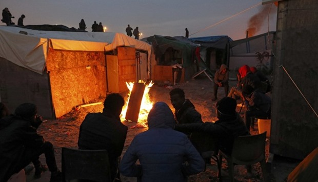 Migrants sit near a fire for warmth at the end of the first day of the evacuation