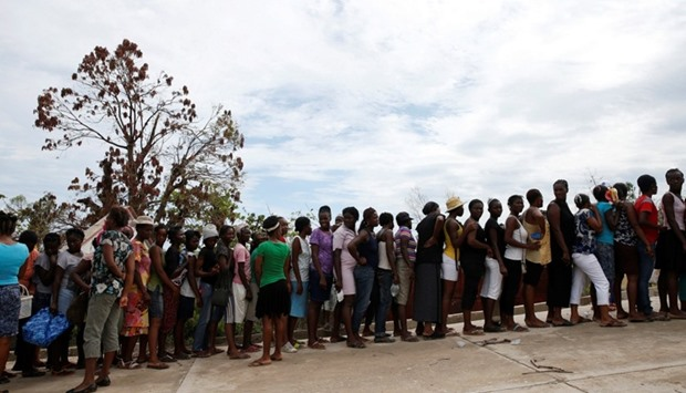 People make a line as they wait for food to be handed out after Hurricane Matthew hit Jeremie, Haiti