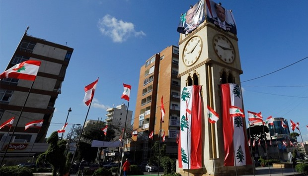 clock tower covered in Lebanese flags ahead of a parliament session expected to elect former general