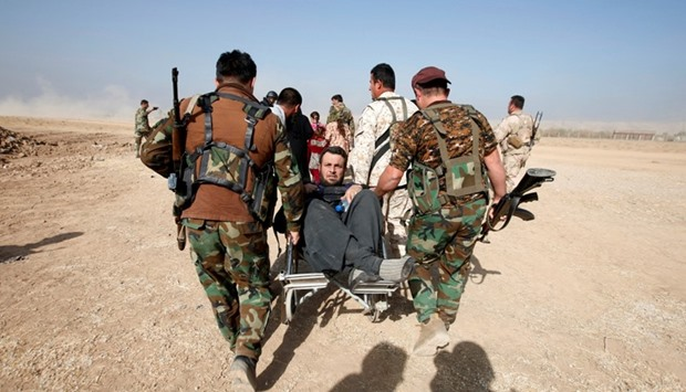 Kurdish Peshmerga fighters carry a wheelchair-bound man, Abbas Ali, 42, after he escaped with his wi