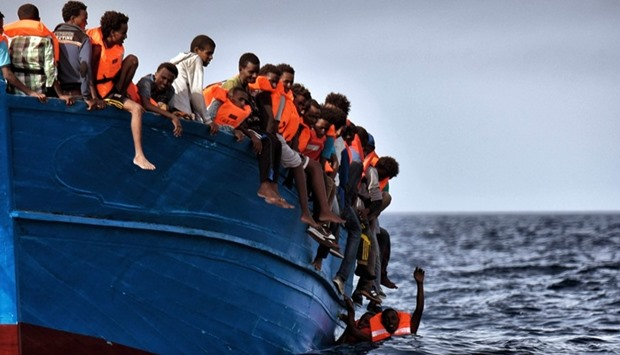 Migrants hang from a boat as they wait to be rescued as they drift in the Mediterranean Sea