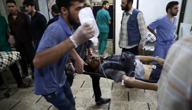 An injured Syrian man arrives on a stretcher to receive treatment at a makeshift hospital