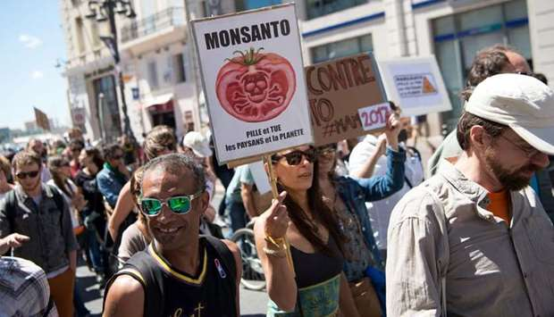 Demonstrators walk with a placard reading 'Monsanto robs and kills farmers and our planet'
