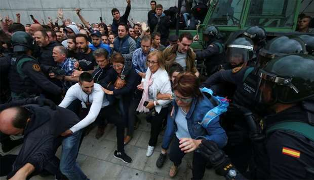 Spanish Civil Guard officers disperse people from the entrance of a polling station for the banned i