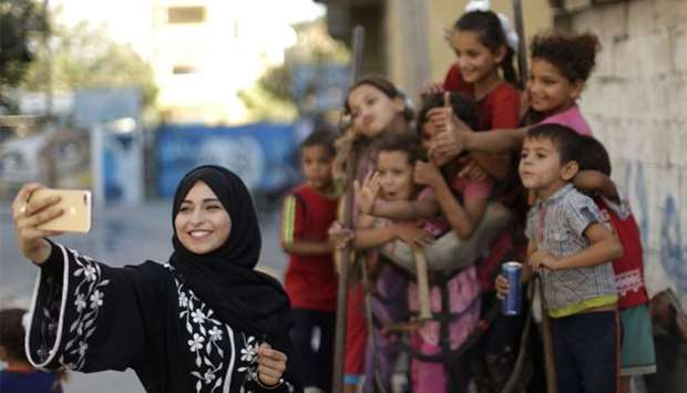 Palestinian Fatma Abu Musabbeh uses her mobile phone to take pictures of children for her social med