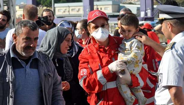 """A member of the Red Cross holds a child as migrants disembark from rescue ship Aquarius run by NGO """""""