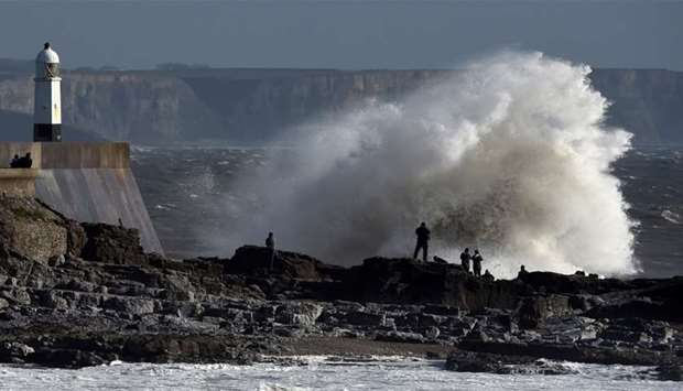 Waves crash over the lighthouse as storm Ophelia approaches Porthcawl, Wales