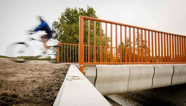 A Cyclist rides over what has been named as the world's first 3-D printed concrete bridge after its