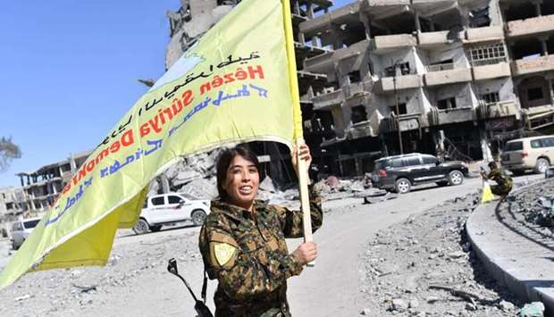 Rojda Felat, a Syrian Democratic Forces (SDF) commander, waves her group's flag at the iconic Al-Nai