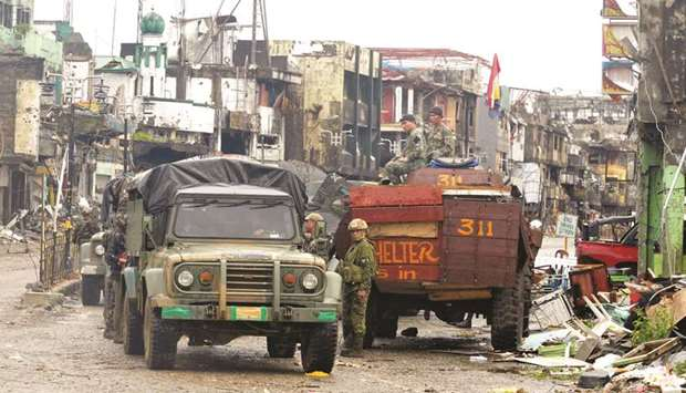 Government troops guard in front of destructed houses and buildings in Bangolo town, Marawi city.