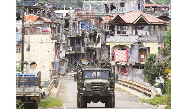 Soldiers on a military truck drive past houses and buildings damaged after government troops cleared