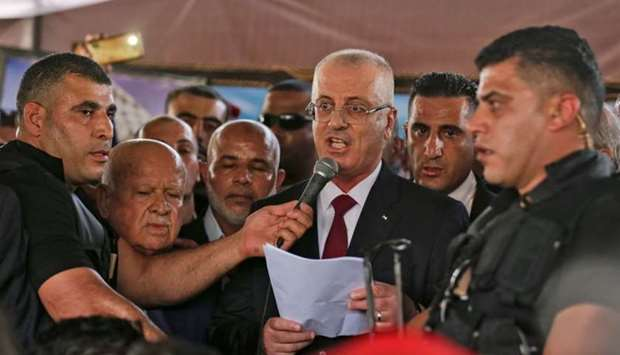 Palestinian prime minister Rami Hamdallah (C) makes a statement after his arrival at Beit Hanun in t