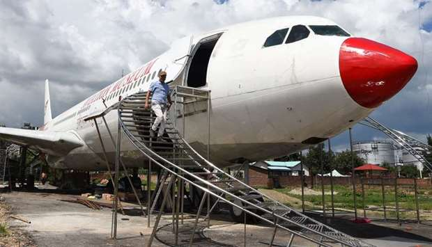 Nepali pilot Bed Upreti walks from an airplane that has been converted into an aviation museum in Ka