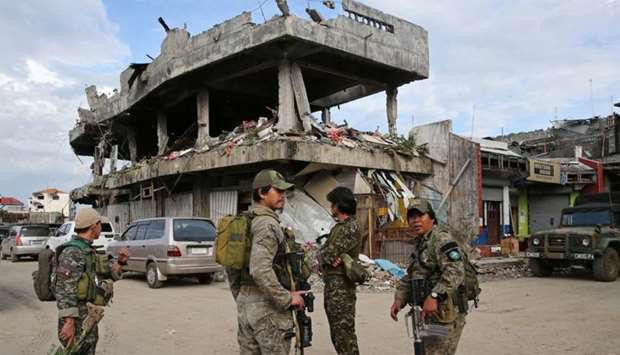 Soldiers stand on guard in front of a damaged building  in Marawi City
