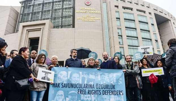 """Protesters hold a banner that reads, """"Free rights defenders"""" during a rally outside the court house"""