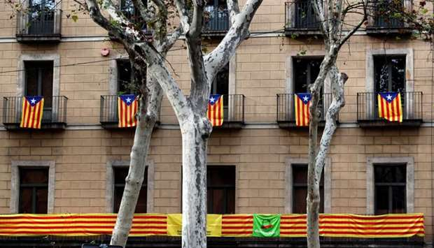 Catalan flags hang from balconies the morning after the Catalan regional parliament declared indepen