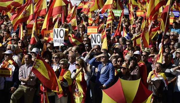 "People hold signs reading ""No to the coup"" while waving Spanish flags during a demonstration calling"