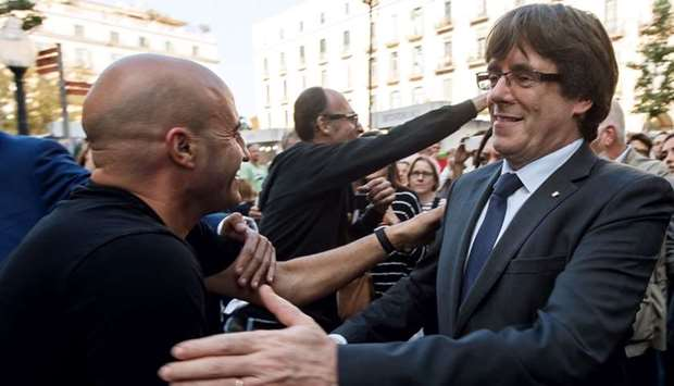 Catalan regional president Carles Puigdemont (R) is greeted by residents in Girona