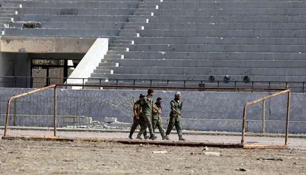 Fighters of Syrian Democratic Forces walk at the stadium in Raqqa, Syria