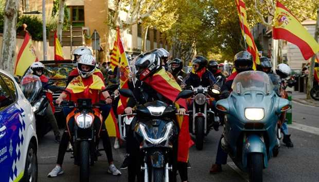 Some people on bikes ride wrapped in Spanish and Catalan flags during a demonstration calling for un