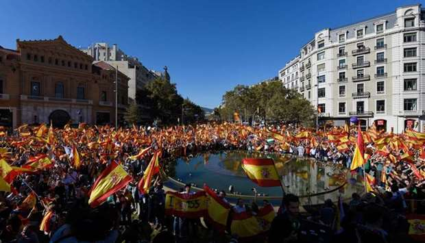 Protesters wave Spanish and Catalan Senyera flags during a pro-unity demonstration in Barcelona