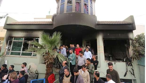 People gather at the Patriotic Union of Kurdistan (PUK) building after it was burnt overnight, in th