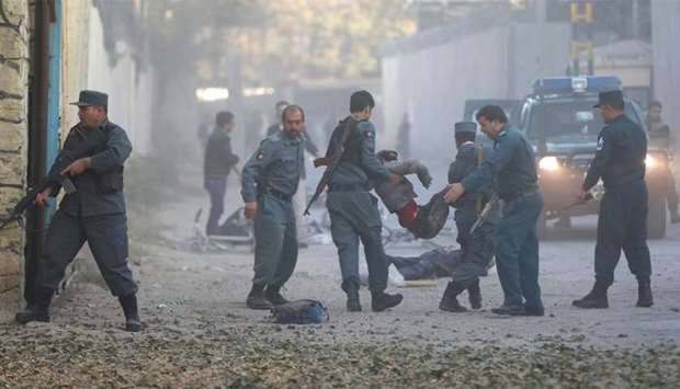 Afghan policemen carry an injuried after a blast in Kabul, Afghanistan