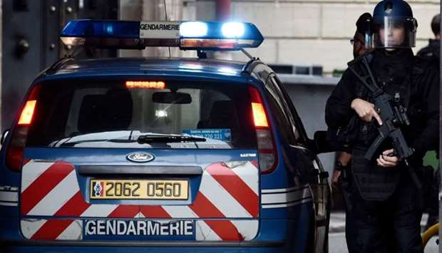 Armed French policemen stand guard