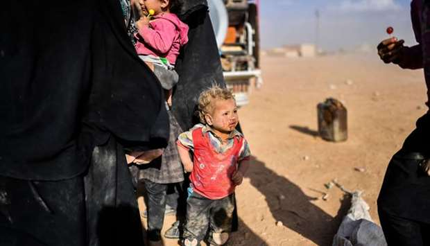 Syrians displaced from the city of Deir Ezzor gather on the outskirts of Raqqa yesterday.
