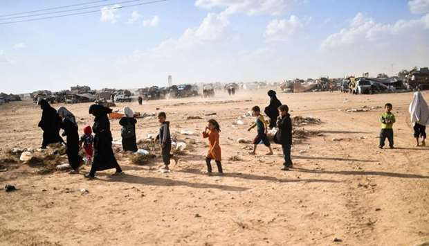 Syrians displaced from the city of Deir Ezzor walk on the outskirts of Raqa on October 2, 2017