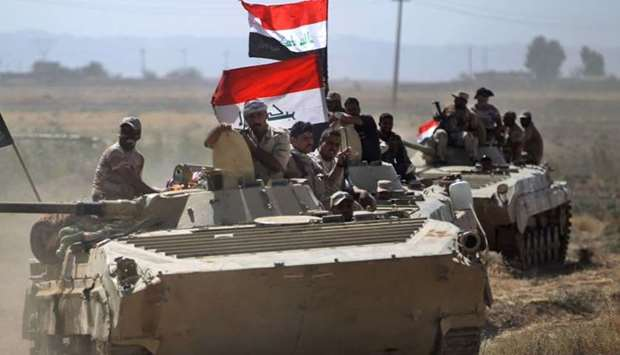 Iraqi forces advance during an operation to recapture the town