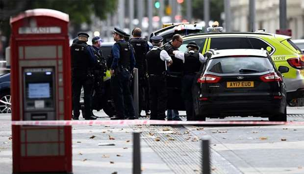 Police officers stand next to and enter a car in the road near the Natural History Museum, after a c