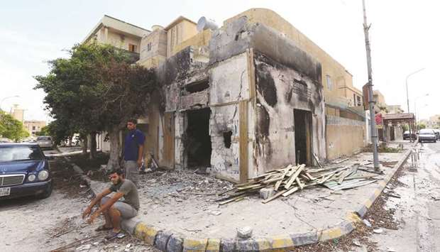 Libyans sit next to a damaged house in Sabratha yesterday, after three weeks of deadly fighting.