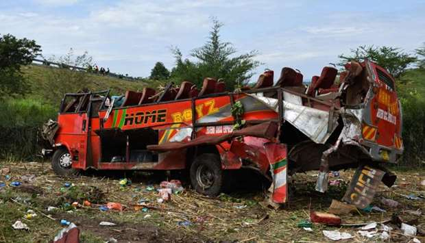 Kenyan emergency personnel and security forces inspect the wreckage of a bus at the site of an accid