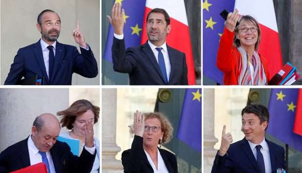 Members of the French government point towards the sky as they leave after the weekly cabinet meetin