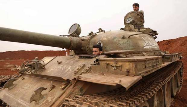 Syrian rebel-fighters from the National Liberation Front (NLF) secure a tank