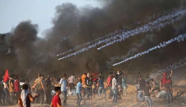 Tear gas canisters are fired by Israeli troops towards Palestinian demonstrators during a protest ca