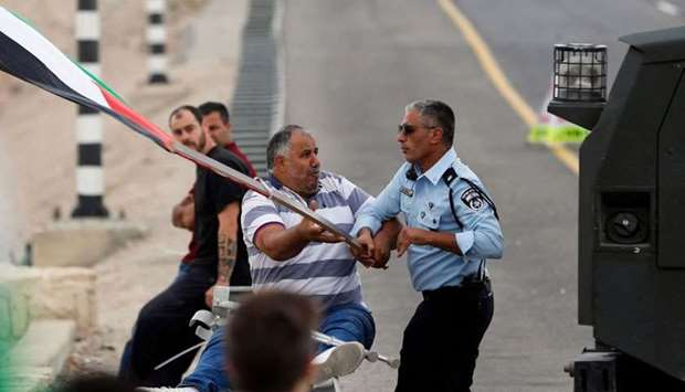 An Israeli policeman attempts to take a flag away from a Palestinian