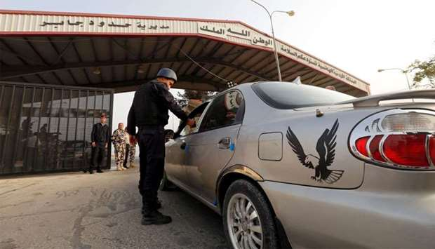 A Jordanian policeman checks a car at Jordan's Jaber border crossing checkpoint near Syria's Nasib c