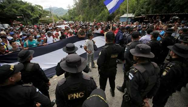 Guatemala's police officers stand as Honduran migrants, part of a caravan trying to reach the US