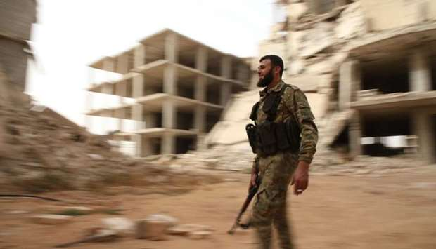 A Syrian rebel-fighter from the National Liberation Front (NLF) walks in a street in the rebel-held