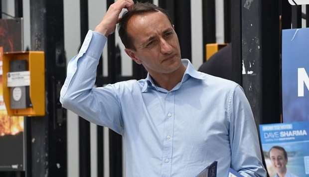 Liberal Party candidate for Wentworth Dave Sharma (L) waits for voters outside a polling station