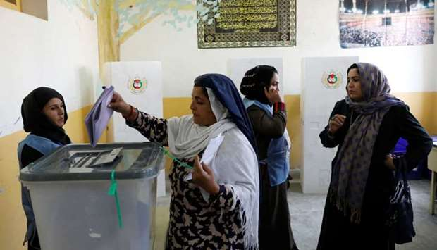 An Afghan woman casts her vote during parliamentary elections at a polling station in Kabul, Afghani