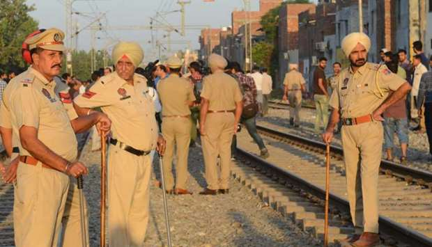 Indian Punjab Police personnel stand guard at the scene of an accident along railroad tracks in Amri