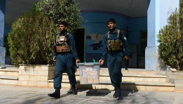 Afghan policemen carry a ballot box after ballots were counted, in Herat province