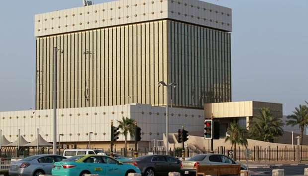 Cars drive past the building of the Qatar Central Bank in Doha